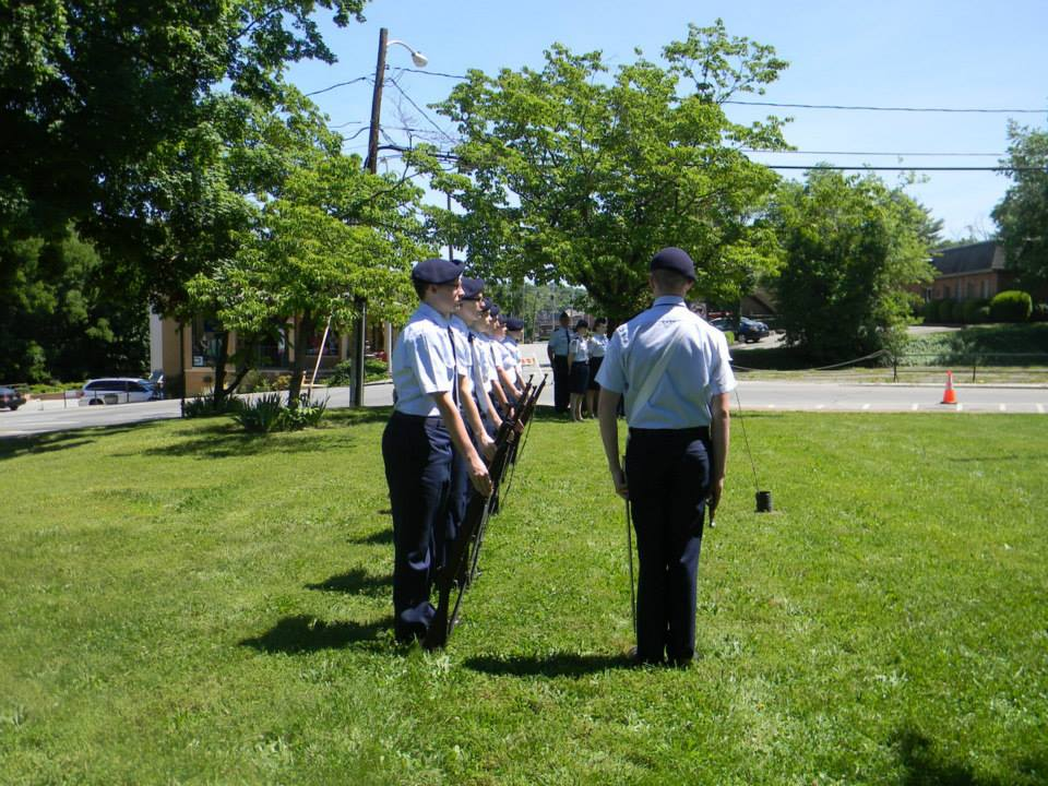 Servicemembers in blue, standing at attention